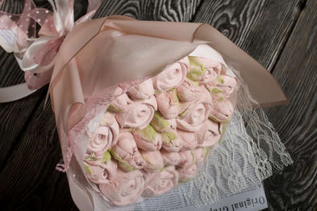 Marshmallow bouquet in paper packaging. Zephyr in the form of roses and tulips. In pink. Close-up shot.
