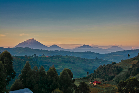 Uganda volcanoes with morning clouds and layered colored sky