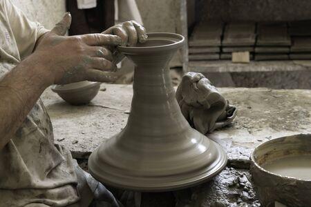 Nahaufnahmehände mit Töpferscheibe, die große Keramikvase herstellt Standard-Bild