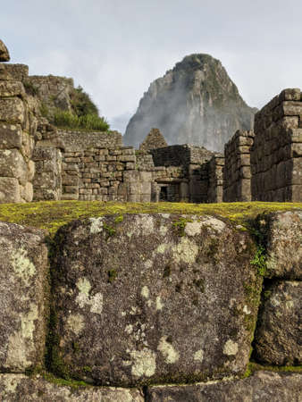 Misty peak of Huayna Picchu in distance with stone walls of Machu Picchu in foreground