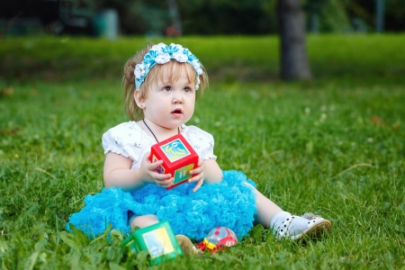 Baby with toys sitting on the green grass