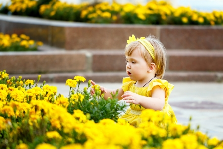 Girl in a yellow dress sits near a flower bed with yellow flowers Stock Photo