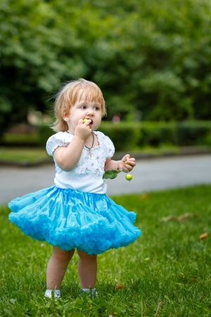 winesap apple: Little blond girl in a blue skirt eating an apple