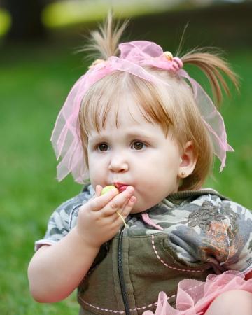 Little blond girl in a blue skirt eating an apple