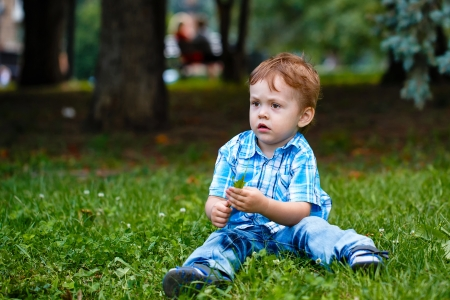 chemise carreaux: Petit gar�on en jeans et une chemise � carreaux, assis sur l'herbe dans le parc