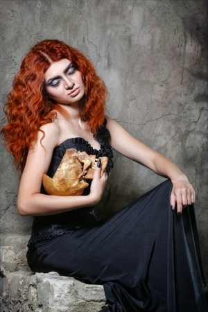 headbone: Red-haired vampire girl posing with a skull in her hands in urban twilight Stock Photo