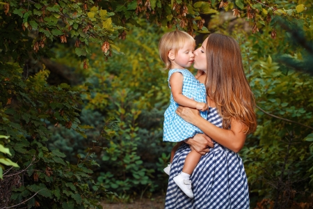 Mother holds daughter in his arms and kisses her on the cheek Stock Photo - 21644533