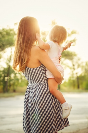 blissfulness: mother holds daughter on hands against the beautiful sunset