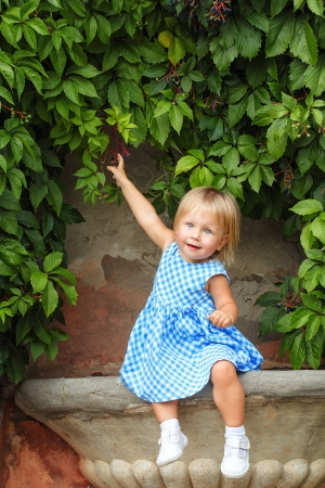 Little blonde girl on a background of green grape leaves