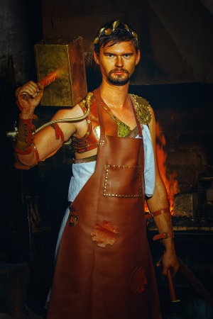 Hephaestus blacksmith in a leather apron in a forgery with a hammer on the shoulder
