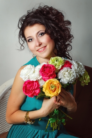 Girl in a dress holding a bouquet of flowers. Photographed in the studio photo
