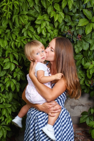 Mother holds daughter in his arms and kisses her on the cheek Stock Photo - 21757314