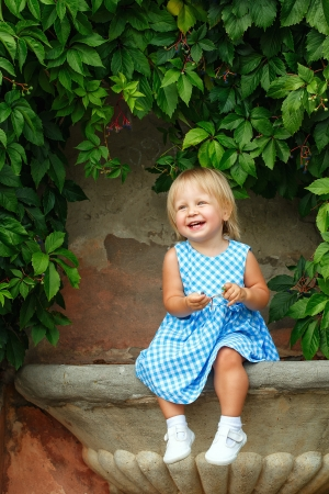 babby: Little blonde girl on a background of green grape leaves