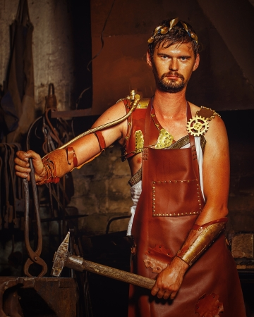 Hephaestus blacksmith in a leather apron in the blacksmith with hammer and clippers, anvil Stock Photo
