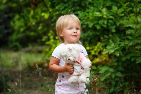 Blond girl with blue eyes holding a teddy bear photo