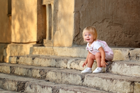 Blond girl with blue eyes sitting on the porch steps photo