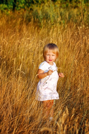 Blonde girl walking through the ears of wheat at sunset photo