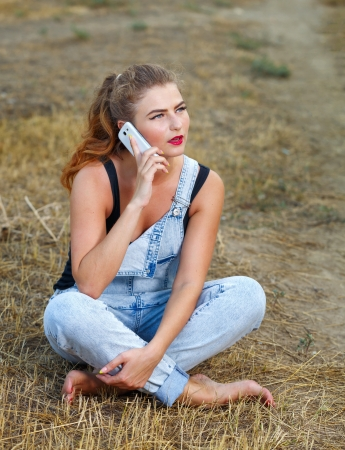 Beautiful pin-up girl in denim overalls and a T-shirt, with a cell phone in his hand on outdoors Stock Photo - 22036496