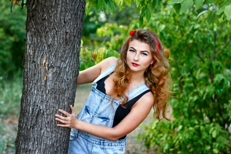 Beautiful pin-up girl in denim overalls and a a red kerchief hiding behind a tree Stock Photo - 22110730