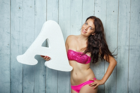 Beautiful girl in a bathing suit holds in hands letter Stock Photo - 22110732