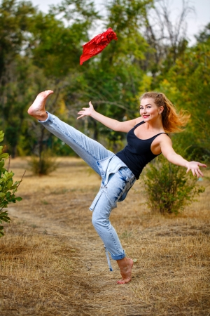 Beautiful pin-up girl barefoot in jeans overalls throws a red bandanna photo