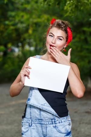 Beautiful pin-up girl in denim overalls and a red bandana holding copyspace Stock Photo - 22114891