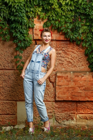 Beautiful pin-up girl in denim overalls and a T-shirt outdoors photo