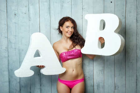 Beautiful girl in a bathing suit holds in hands letters Stock Photo - 22139828