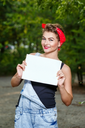 Beautiful pin-up girl in denim overalls and a red bandana holding copyspace Stock Photo - 22168517