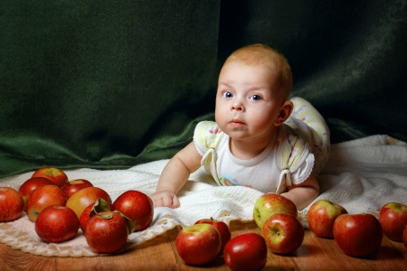 blissfulness: Redhead babe lying among ripe apple and smiling at the camera Stock Photo