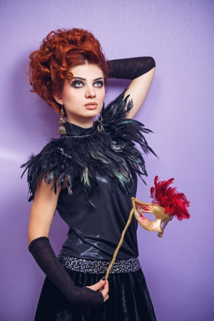 upsweep: Portrait of red-haired lady in evening dress holding a mask Stock Photo