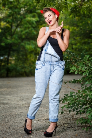 Beautiful pin-up girl in denim overalls and a T-shirt outdoors Stock Photo - 22252614