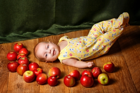 winesap apple: Redhead babe lying among ripe apple and smiling
