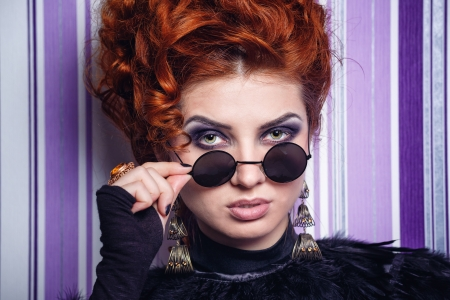 makeups: Red-haired girl with makeup looking over sunglasses photographed close-up