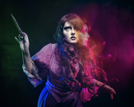 Girl in the image of a witch with a magic wand shot in studio