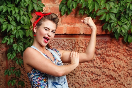 Beautiful pin-up girl in denim overalls and a red bandana  winks and demanstriruet bicep
