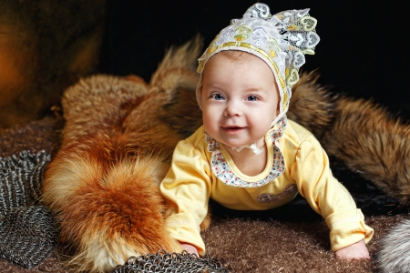 peltry: Blue-eyed baby lying on fur litter near the hauberk, fox pelt in the background