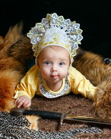 peltry: Blue-eyed baby lying on fur litter near the hauberk and sword Stock Photo