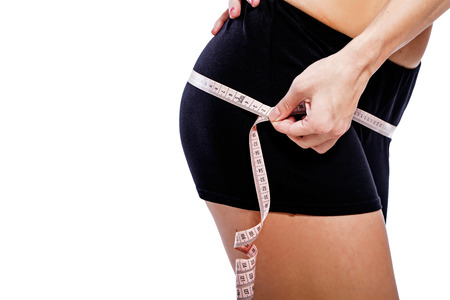 Girl measuring hip circumference after a grueling workout, isolated on white