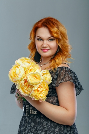 Attractive red-haired girl holding a bouquet of yellow flowers Stock Photo - 22706668