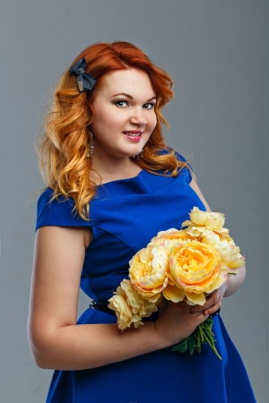 Attractive red-haired girl holding a bouquet of yellow flowers Stock Photo - 22853557