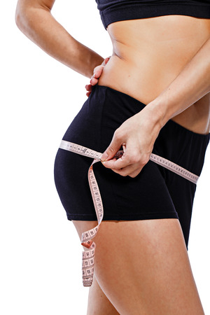 regimen: Girl measuring hip circumference after a grueling workout, isolated on white background