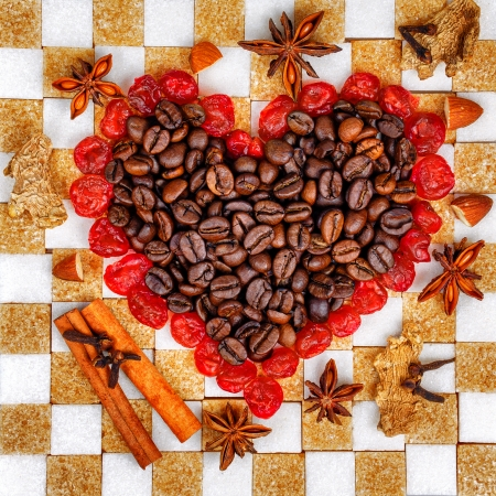 Heart of the coffee and cherries laid out on chessboard made ​​of sugar cubes photo