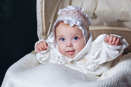 Cheerful and happy blue-eyed baby in  bonnet lies in cradle
