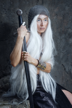 Girl with long white hair in chain mail and sword Stock Photo
