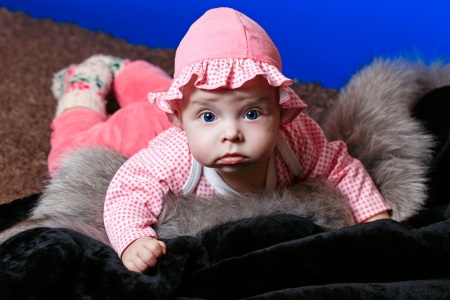furskin: Baby with blue eyes lying on fur and looking at the camera Stock Photo