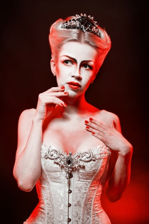 makeups: Red Queen with a crown and a corset, with make-up in studio shot