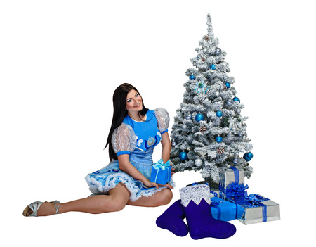 Attractive young girl sitting near Christmas tree and gifts photo
