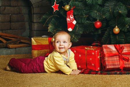 Redhead babe with blue eyes lies near the Christmas tree and gifts Stock Photo - 24236879