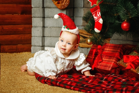 Redhead babe with blue eyes lies near the Christmas tree and gifts Stock Photo - 24236880